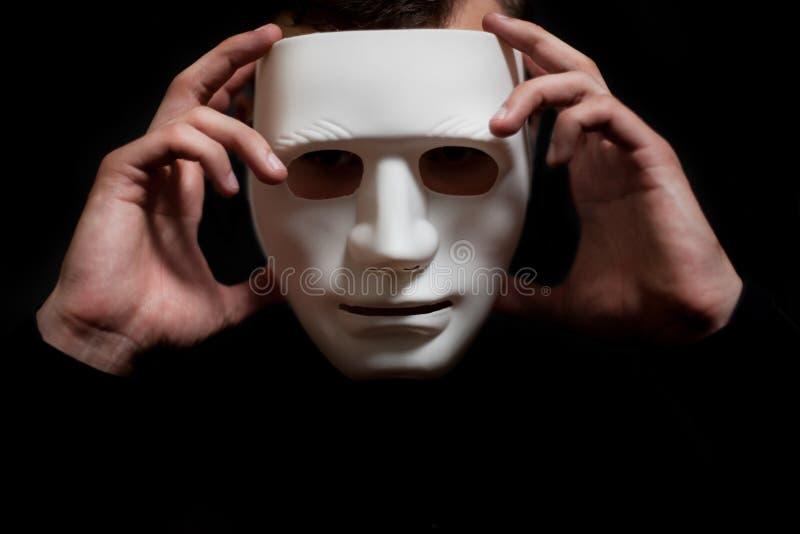 L'uomo decolla la maschera bianca dal suo fronte fotografia stock libera da diritti
