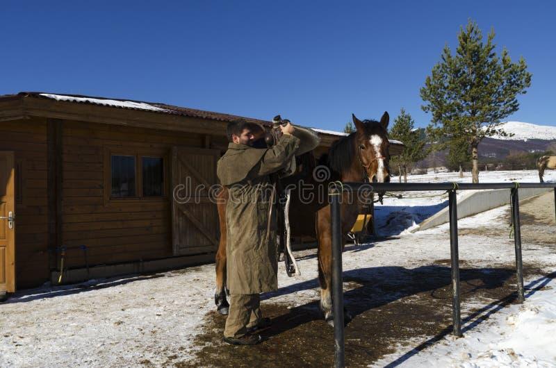 L'uomo decolla la sella del cavallo fotografia stock