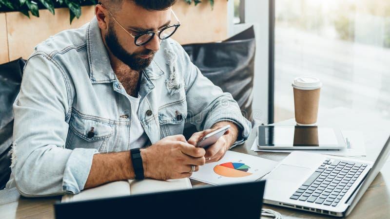 L'uomo dei pantaloni a vita bassa si siede in caffè, utilizza lo smartphone, lavora a due computer portatili L'uomo d'affari legg immagini stock