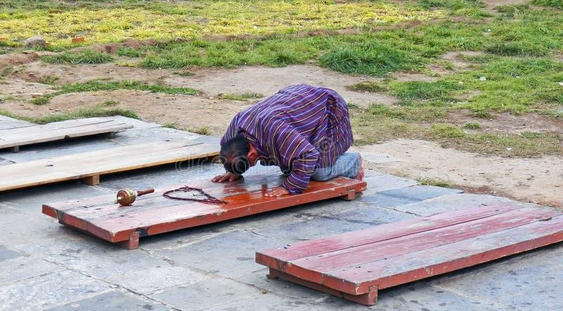 L'uomo del Bhutanese esegue una prostrazione per che il suo il quotidiano prega al Buddha fotografia stock