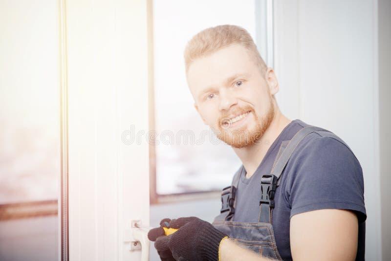 L'uomo del lavoratore installa le finestre e le porte di plastica con bianco a doppi vetri fotografia stock libera da diritti