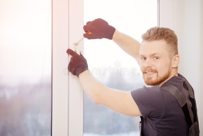 L'uomo del lavoratore installa le finestre e le porte di plastica con bianco a doppi vetri immagine stock libera da diritti