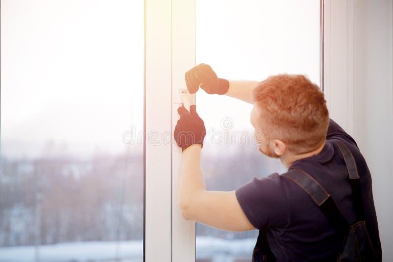 L'uomo del lavoratore installa le finestre e le porte di plastica con bianco a doppi vetri fotografia stock