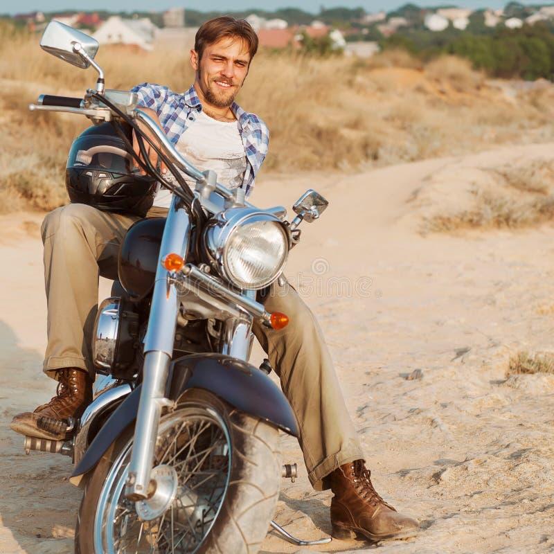 L'uomo del motociclista si siede su una bici fotografia stock libera da diritti