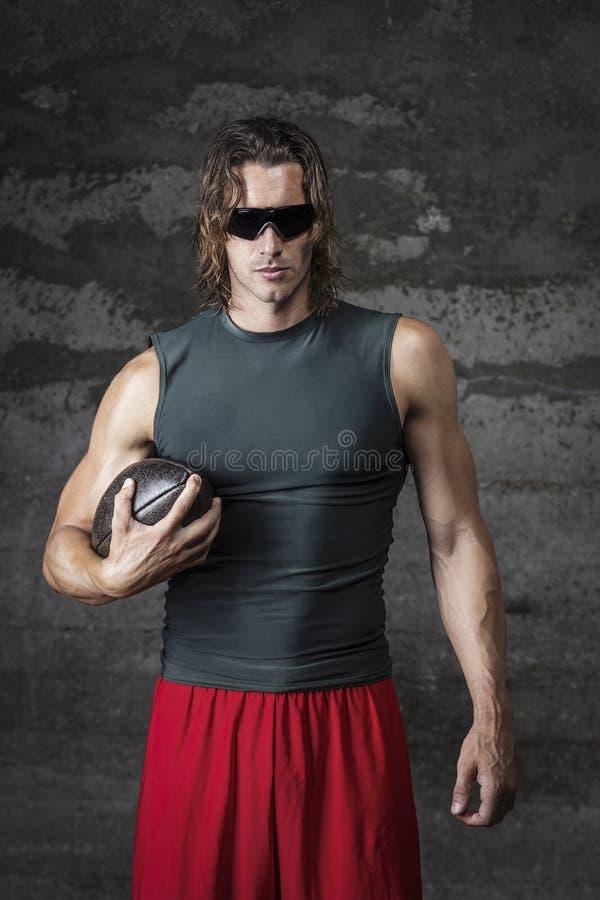 L'uomo del muscolo sta tenendo la palla di calcio fotografia stock libera da diritti