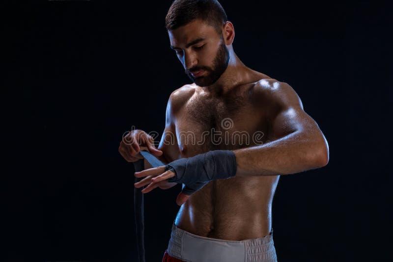 L'uomo del pugile di sport tira gli involucri del polso Modello maschio orientale isolato su fondo nero fotografia stock libera da diritti