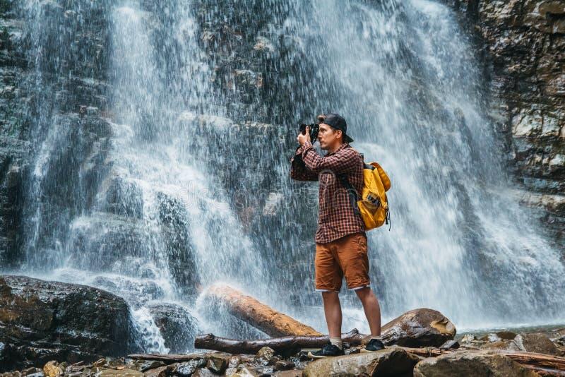 L'uomo del viaggiatore con una condizione gialla dello zaino sui precedenti di una cascata fa un paesaggio della foto Stile di vi immagini stock libere da diritti