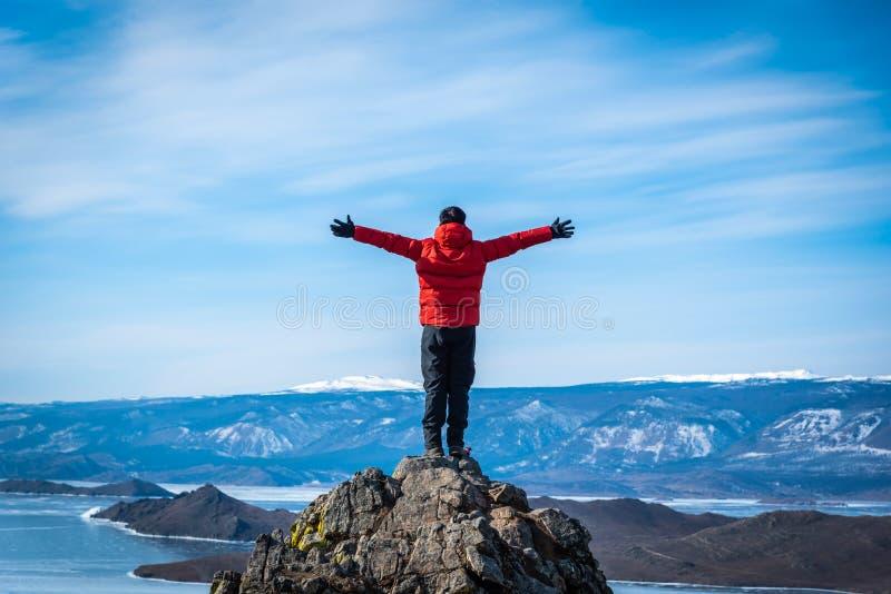 L'uomo del viaggiatore indossa i vestiti rossi e sollevare la condizione del braccio sulla montagna al giorno nel lago Baikal, Si immagine stock libera da diritti