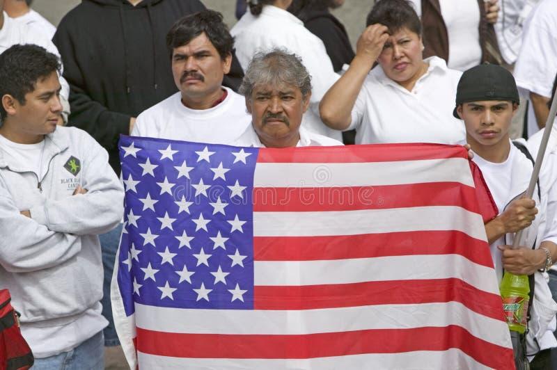 L'uomo dell'America latina tiene la bandiera degli Stati Uniti con le centinaia di migliaia di immigrati che partecipano a marzo  immagini stock libere da diritti