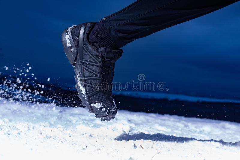 L'uomo dell'atleta sta correndo durante l'esterno di addestramento dell'inverno in tempo freddo della neve immagini stock libere da diritti