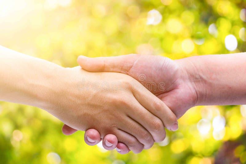 L'uomo della mano stringe le mani sul fondo verde del bokeh immagini stock libere da diritti