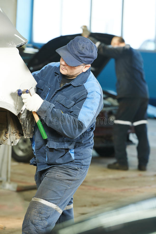 L'uomo della riparazione automatica appiattisce l'automobile del corpo del metallo immagine stock libera da diritti