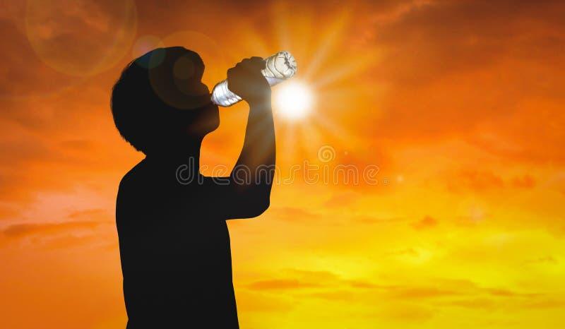 L'uomo della siluetta sta bevendo la bottiglia di acqua sul fondo del caldo con la stagione estiva Concetto dell'onda termica e d immagine stock libera da diritti