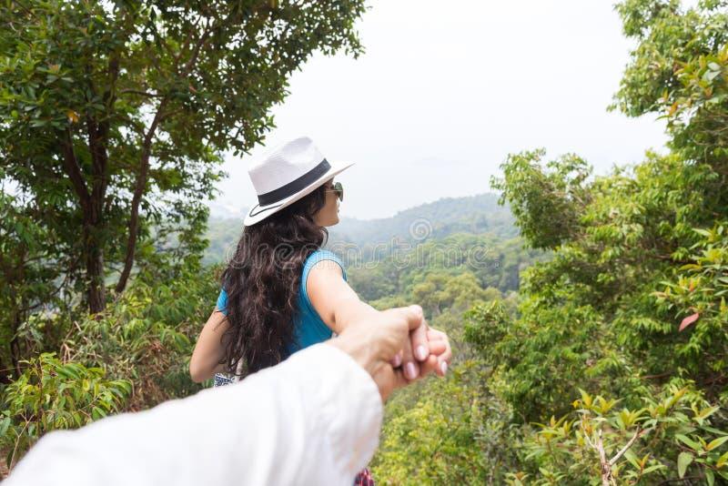 L'uomo della tenuta della donna consegna la bella retrovisione del paesaggio della montagna indietro, giovane turista delle coppi fotografia stock libera da diritti