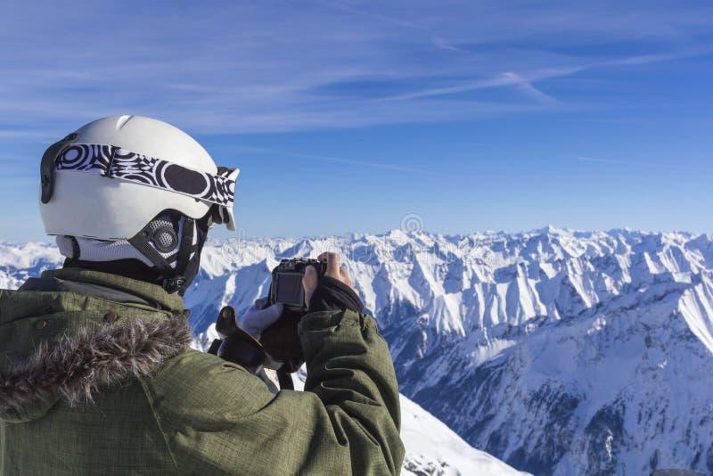 L'uomo dello sciatore con i vetri arancio dello sci in casco bianco fa il photoshoot sulla cima in montagne delle alpi Sui preced fotografia stock libera da diritti