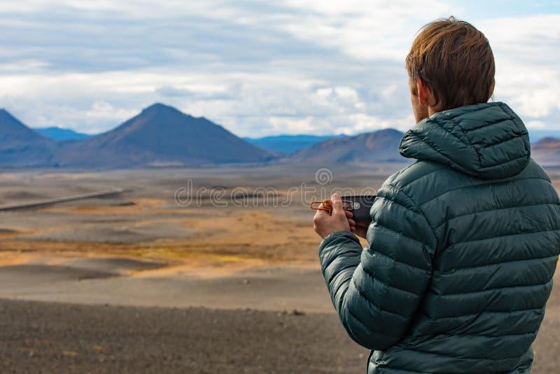 L'uomo di aa ammira il paesaggio con una tazza della bevanda calda Giorno soleggiato di estate in natura con un bello paesaggio d immagini stock libere da diritti