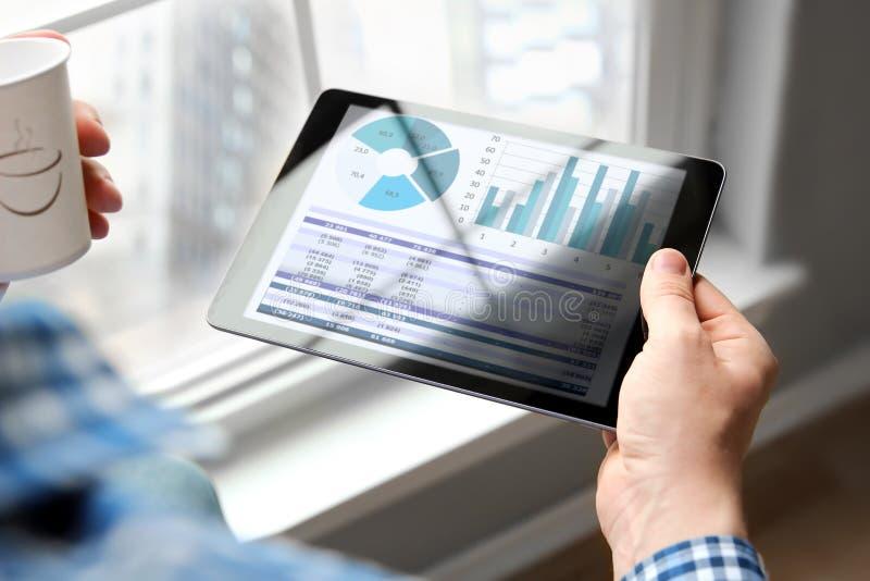L'uomo di affari che lavora e che analizza finanziario dipende i grafici su una compressa nell'ufficio fotografie stock libere da diritti