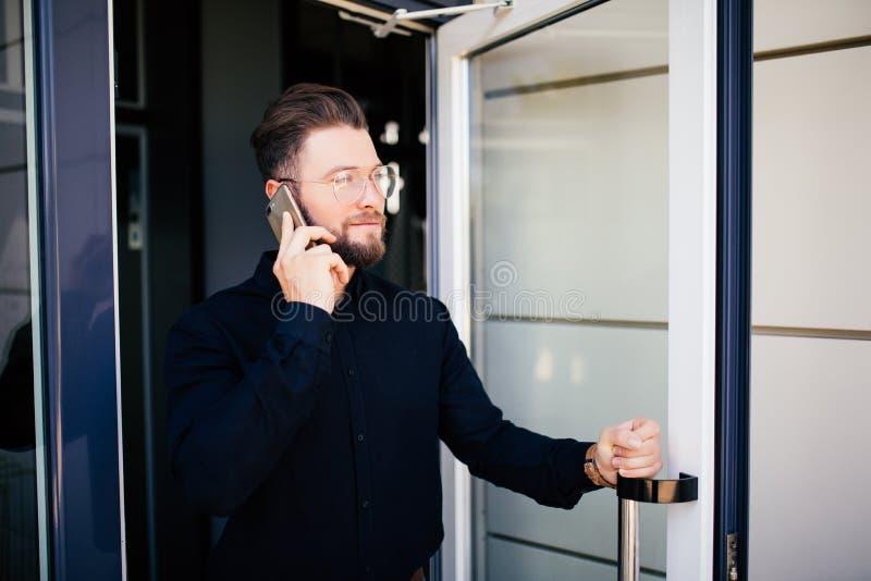 L'uomo di affari che tiene la porta dell'ufficio ed ottiene il bianco all'aperto parla sul telefono L'uomo esce l'uscita dall'edi immagine stock