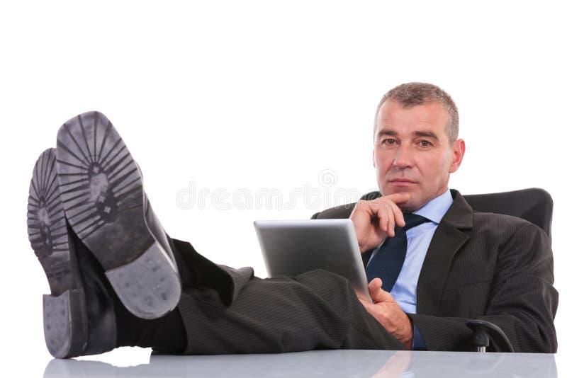 L'uomo di affari con la compressa sta con le gambe sullo scrittorio immagine stock libera da diritti