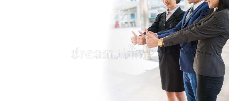 l'uomo di affari e la donna di affari sorridono e mostrano il pollice sulla mano due alla città e lo spazio bianco della copia pe immagine stock libera da diritti