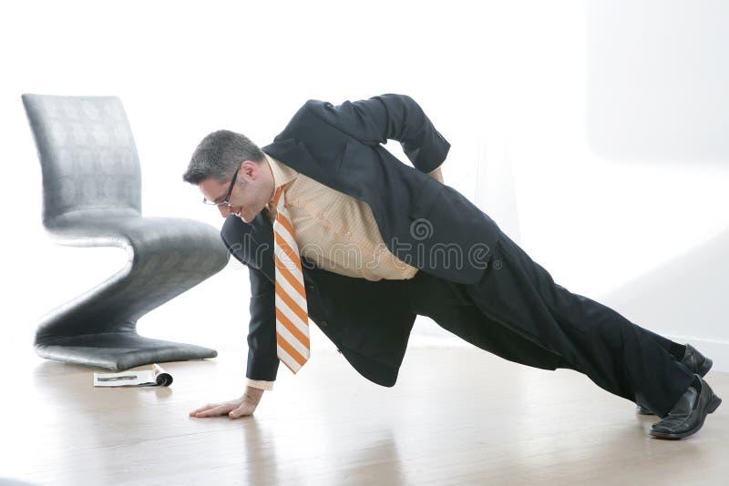 L'uomo di affari fa un Pushup munito fotografia stock