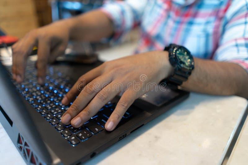 L'uomo di affari facendo uso del computer portatile, si chiude sulla tastiera di battitura a macchina del taccuino della mano Lav immagine stock libera da diritti