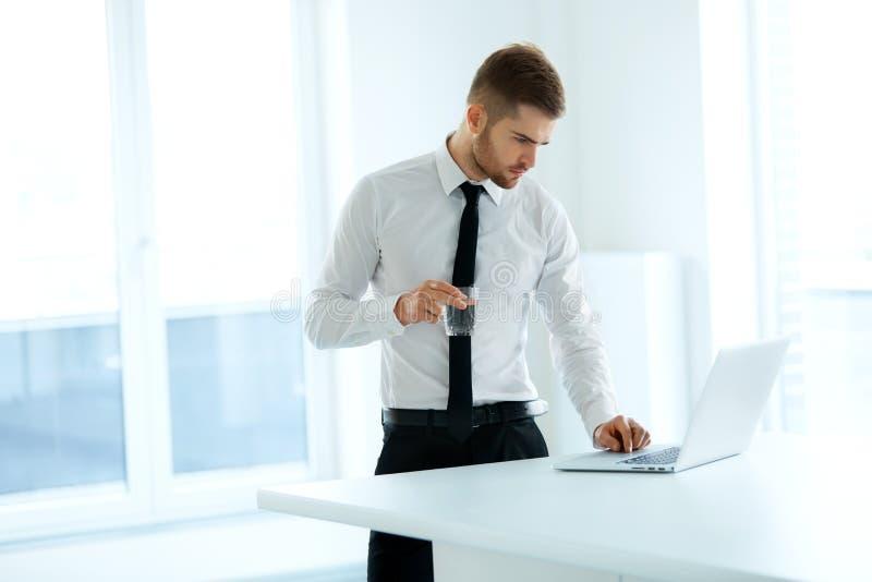 L'uomo di affari lavora al suo computer all'ufficio fotografia stock