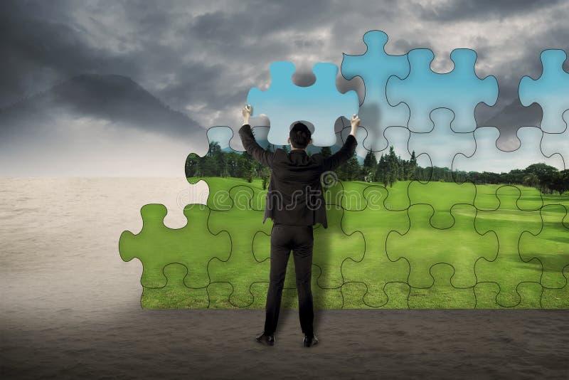 L'uomo di affari monta il puzzle per cambiare dal deserto a paesaggio fotografia stock