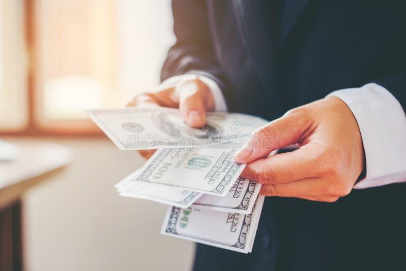 L'uomo di affari passa il conteggio delle fatture di dollaro americano che conservano il concetto immagini stock libere da diritti