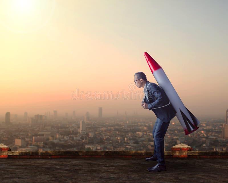 L'uomo di affari porta ancora il missile del razzo sull'alto tetto della costruzione immagini stock