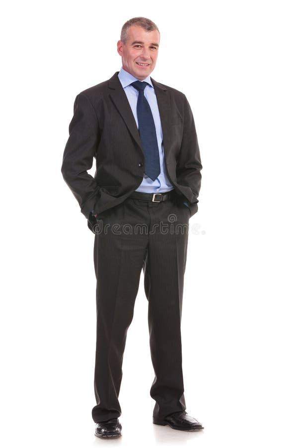 L'uomo di affari sta con le mani in tasche fotografie stock