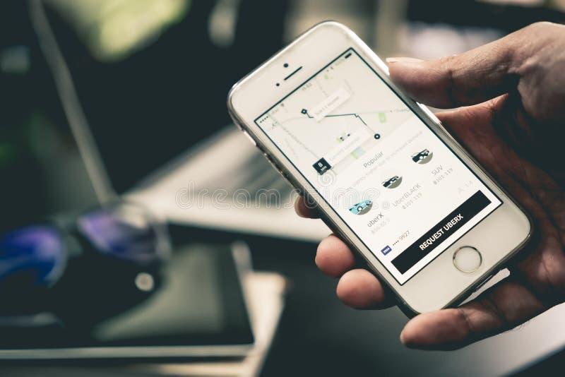 L'uomo di affari sta usando l'applicazione di Uber sul suo iPhone fotografie stock libere da diritti
