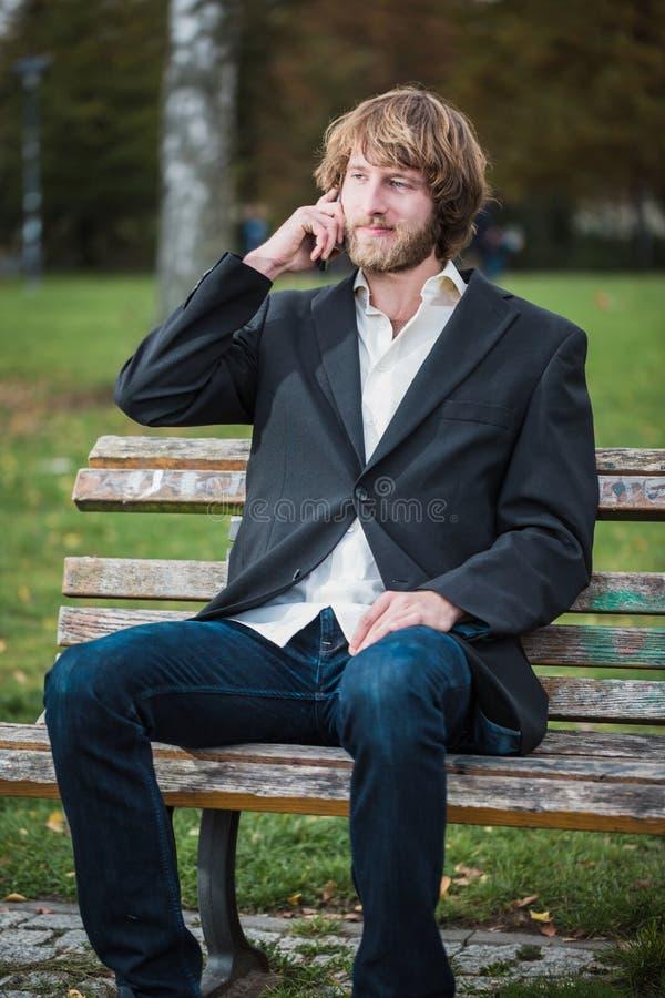 L'uomo di affari sta utilizzando un telefono cellulare al parco fotografie stock libere da diritti