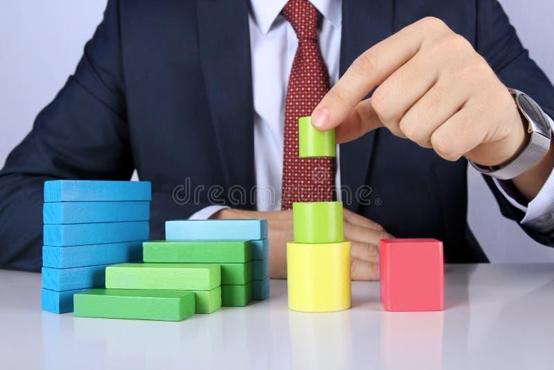 L'uomo di affari sviluppa il diagramma dalle barre di legno dei blocchi immagine stock