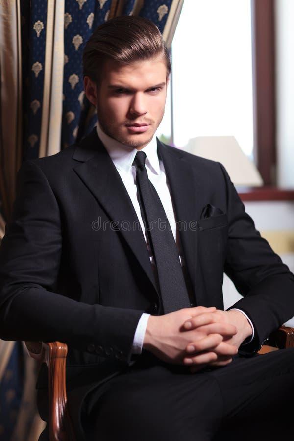 L'uomo di affari vi esamina dalla sedia immagine stock