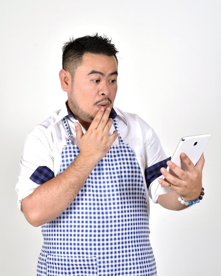 L'uomo di Asian del commerciante in grembiule bianco e blu sta ritenendo il rammarico o boringnwhen ottiene le cattive notizie da fotografia stock libera da diritti