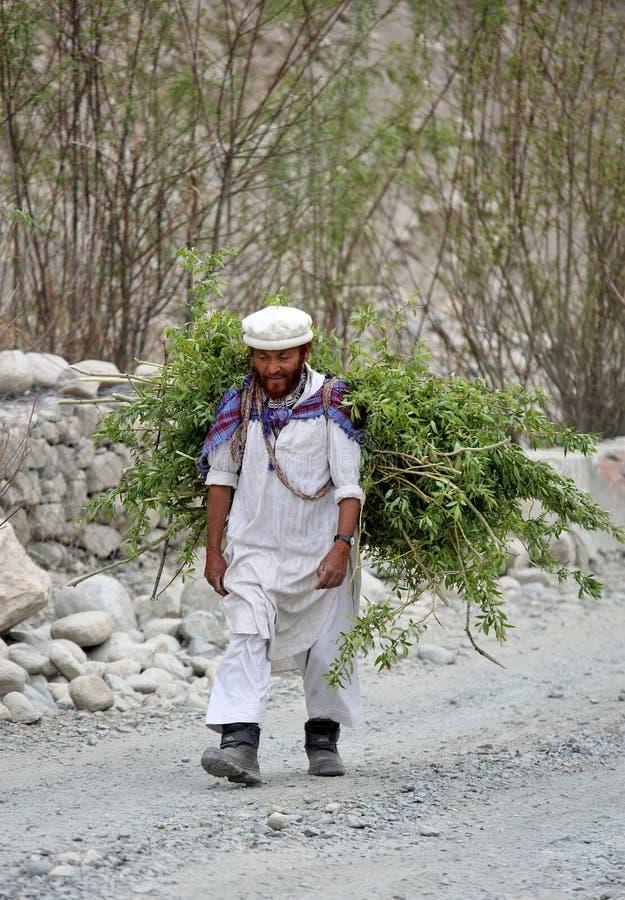 L'uomo di Balti in vestito tradizionale sta portando i ramoscelli ed i rami del salice fotografia stock libera da diritti