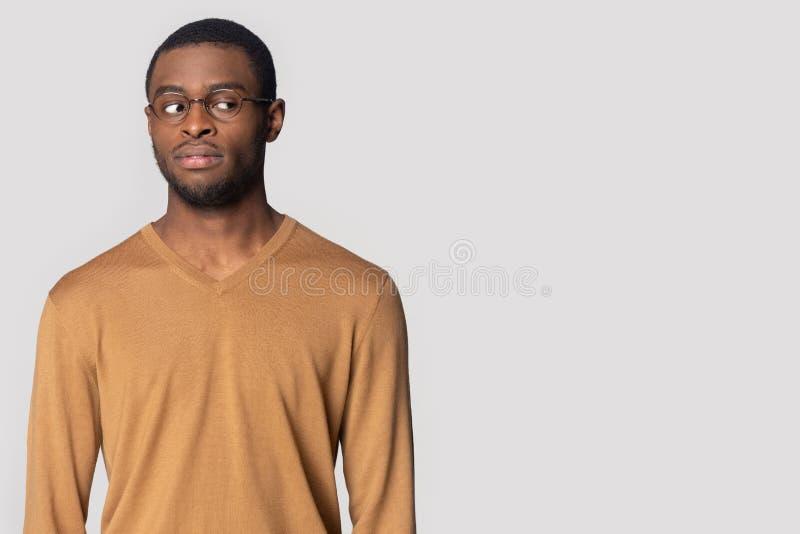 L'uomo di colore pensieroso in vetri esamina lo spazio in bianco della copia fotografia stock libera da diritti