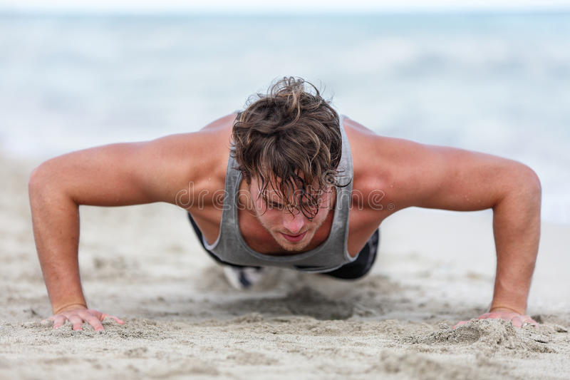 L'uomo di forma fisica fare di armi che di addestramento spinge aumenta l'esercizio immagini stock