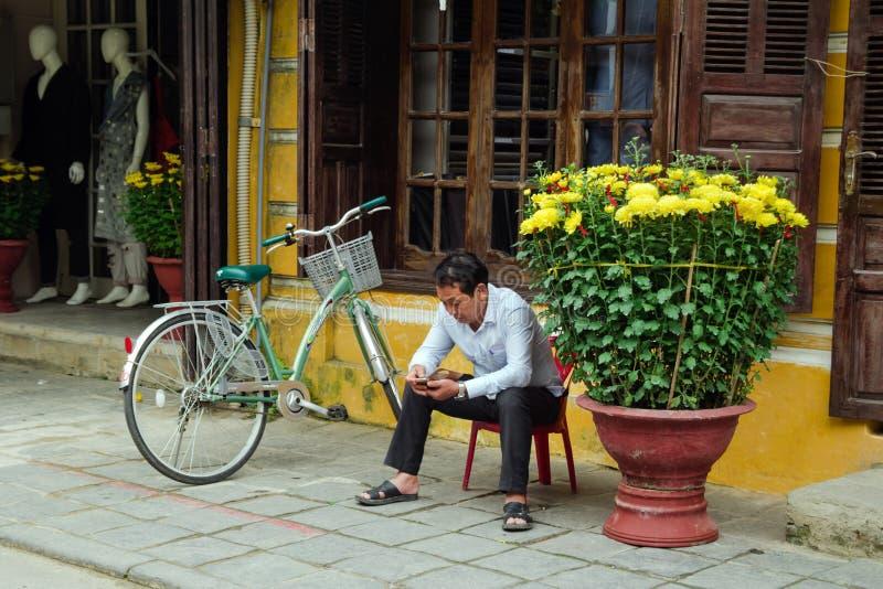 L'uomo di Hoi Local con lo smartphone sta sedendosi su una sedia di plastica vicino per ingiallire la casa con i vasi da fiori co fotografia stock