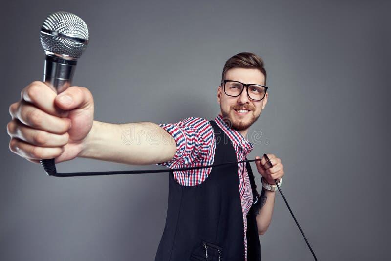 L'uomo di karaoke canta la canzone al microfono, cantante con la barba su fondo grigio Uomo divertente in vetri che tengono un mi fotografie stock