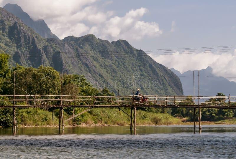 L'uomo di laotiano in motorino passa un ponte di legno sul fiume di Nam Song in Vang Vieng, Laos immagini stock libere da diritti