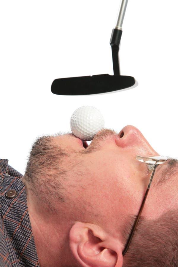 L'uomo di menzogne tiene nella sfera della bocca per il golf della sporgenza fotografia stock libera da diritti