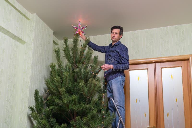 L'uomo di mezza età bello decora un albero di Natale con una stella fotografia stock