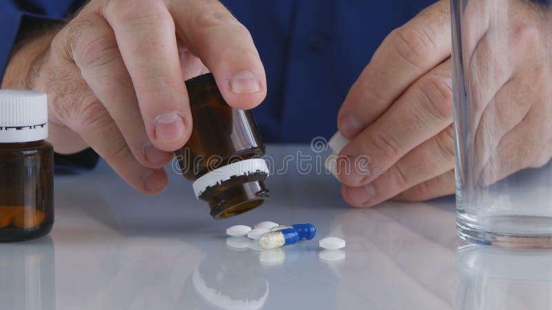 L'uomo di sofferenza che prende le medicine seleziona le pillole a partire dalla superficie di vetro della Tabella immagine stock