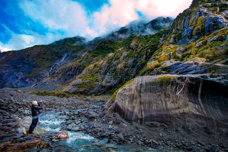 L'uomo di viaggio prende una fotografia in ghiacciaio di Franz Josef importante fotografia stock