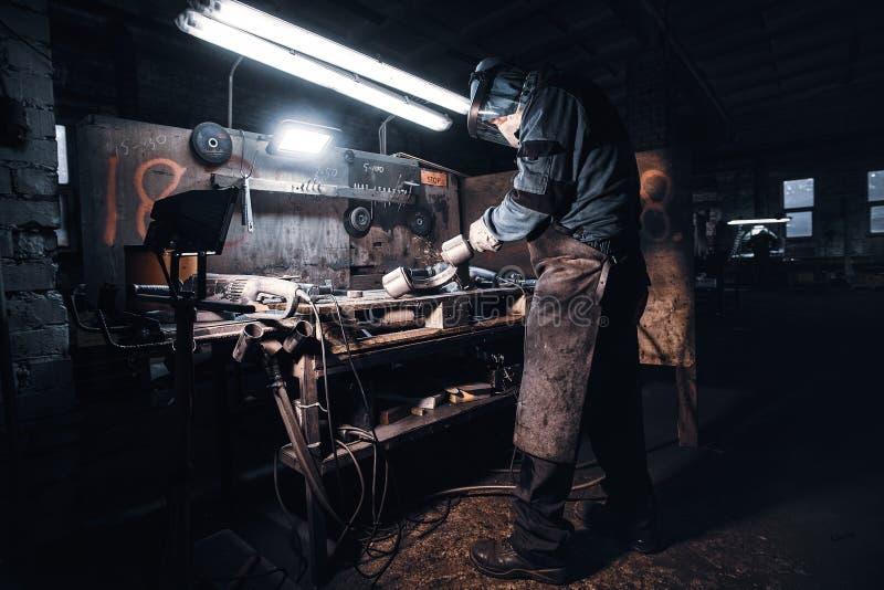 L'uomo diligante lavora con il metallo al laboratorio fotografia stock