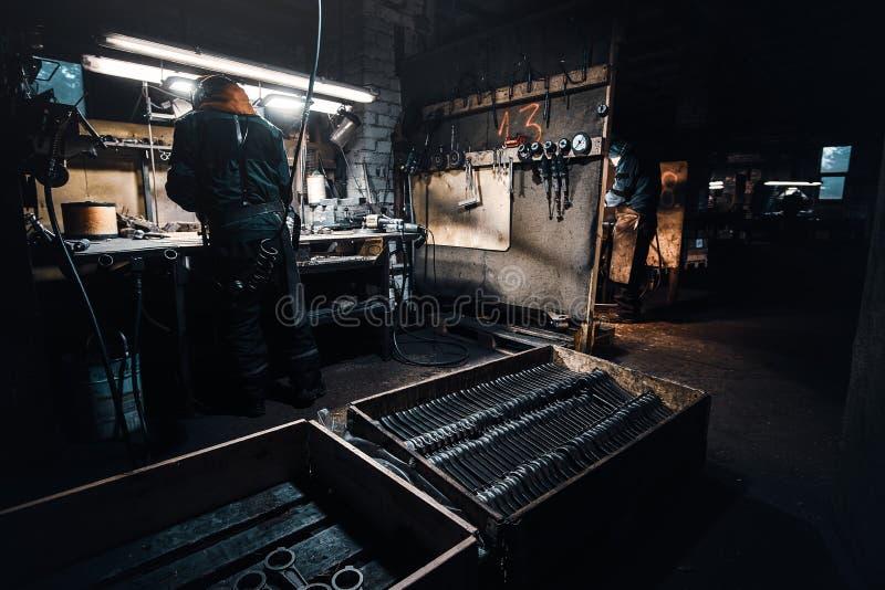 L'uomo diligante lavora con il metallo al laboratorio fotografia stock libera da diritti