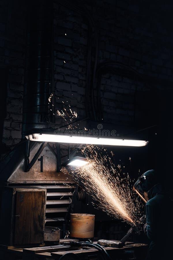 L'uomo diligante lavora con il metallo al laboratorio immagine stock libera da diritti