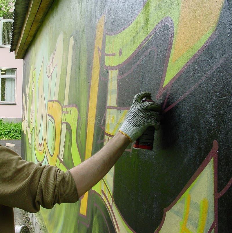 L'uomo dipinge i graffiti fotografie stock